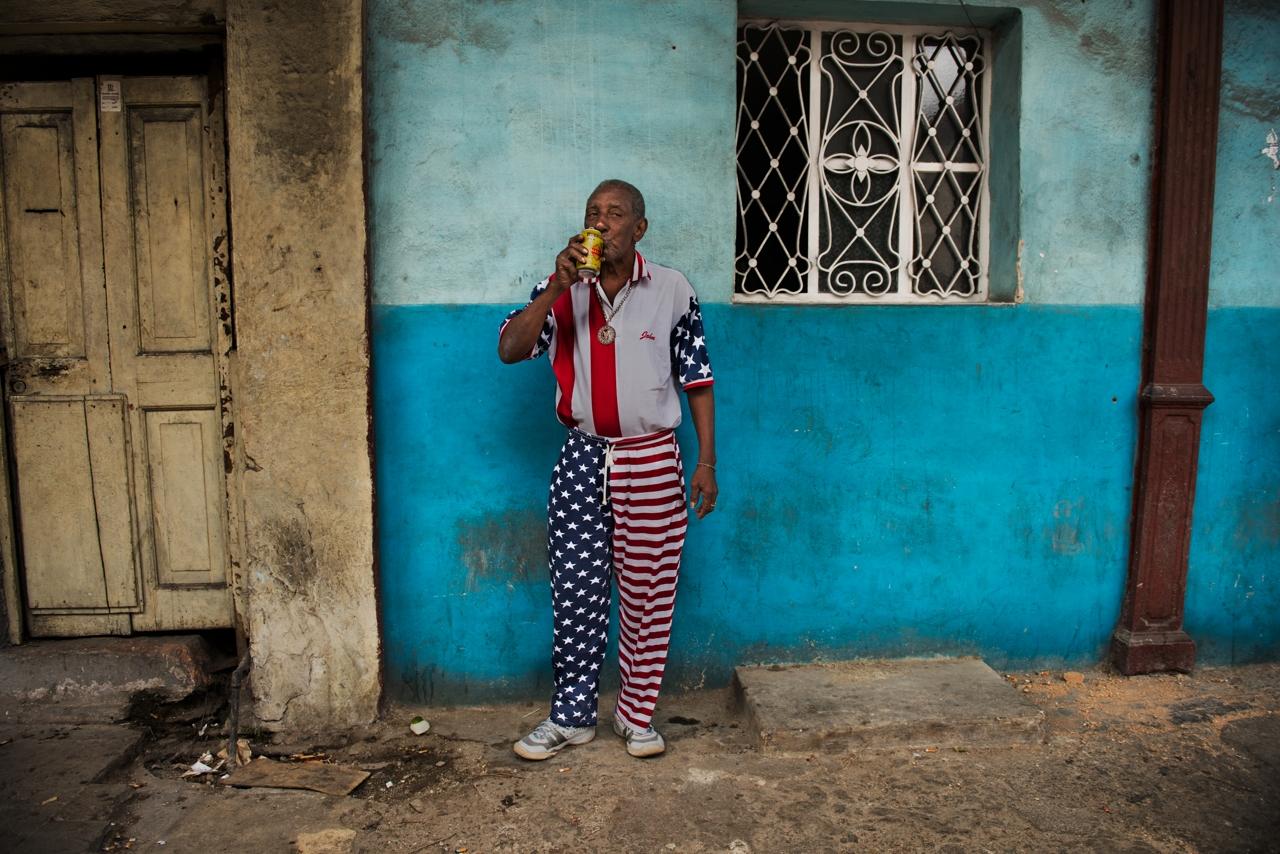 Un cubano indossa i colori della bandiera degli Stati Uniti e beve birra in una strada de L'Avana, Steve McCurry