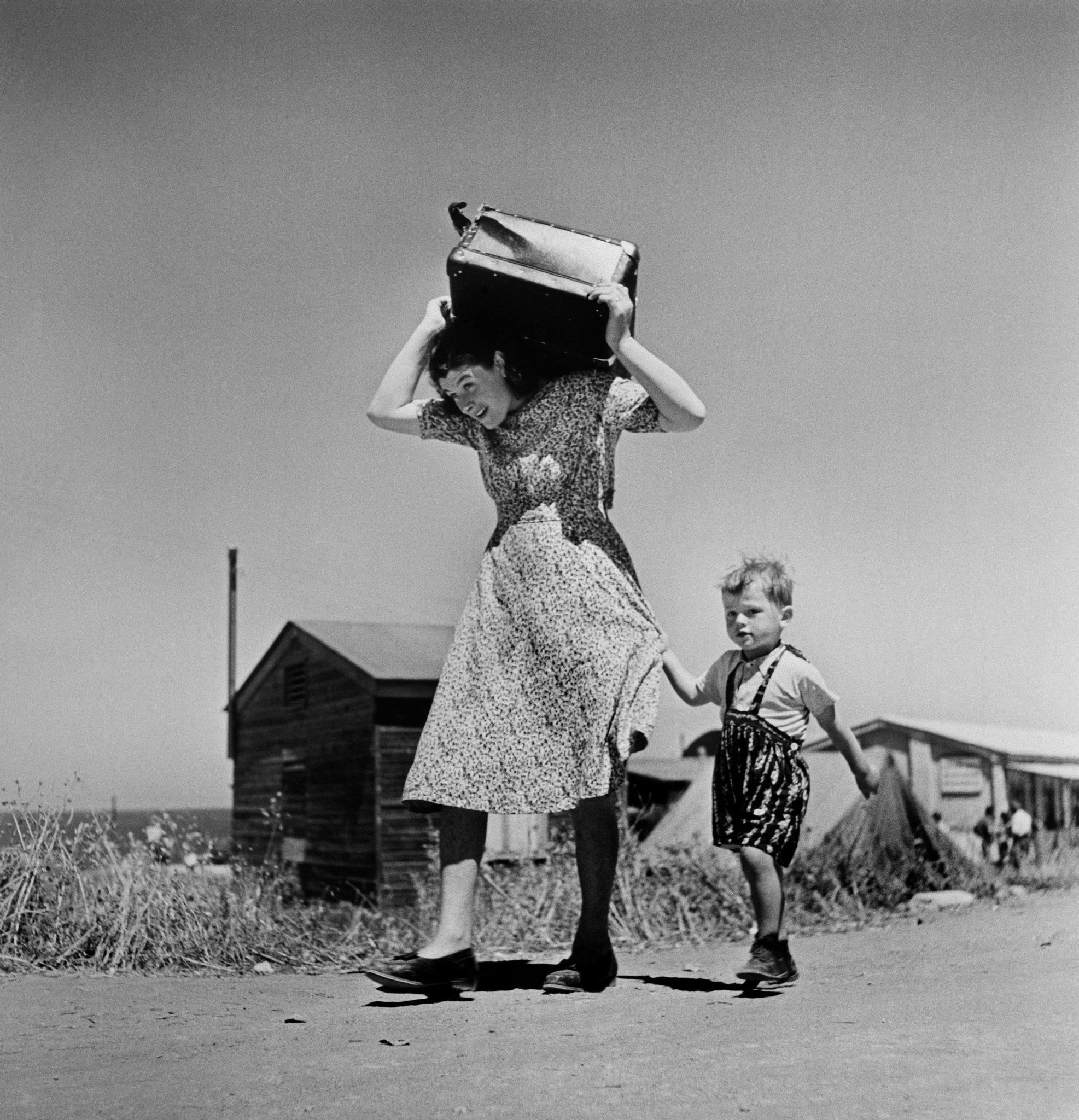 Robert Capa, Woman carrying luggage accompanied by a small boy. Haifa. ISRAEL. 1949-50 @ Magnum Photos
