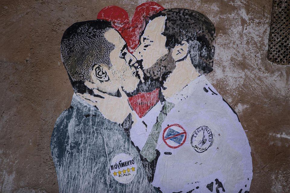 Amor populi sui muri di Roma. Il bacio tra Di Maio e Salvini e la Meloni con Bambino (rifugiato) in braccio