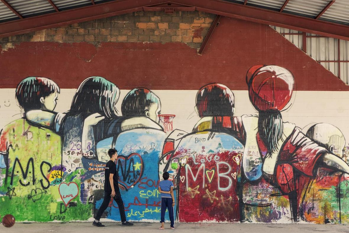 murale effettuato da alcuni bambini rifugiati che rappresenta un gruppo di amici che attraversa un muro