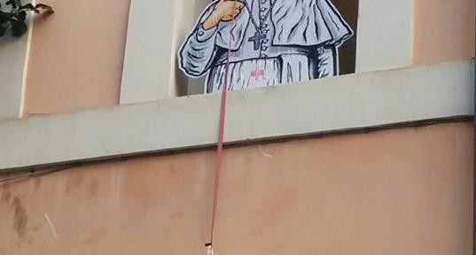 Installazione di Papa Francesco che cala un salvagente per i migranti
