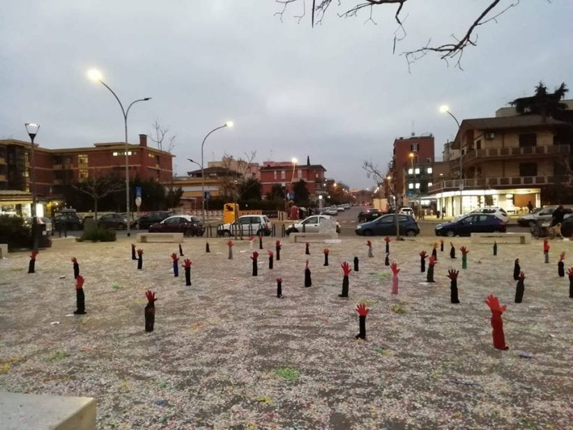 decine di mani di cartone invocano aiuto dall'asfalto