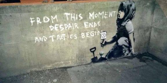 bambino che semina una piantina in un murale attribuito a banksy
