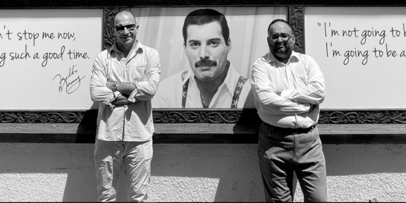 Due imprenditori posano davanti al Freddie Mercury Museum e sullo sfondo il volto del cantante