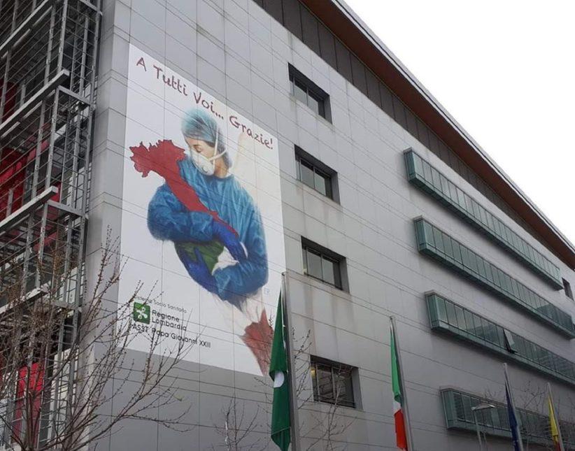 Muraòe Bergamo cin una dottoressa che culla l'Italia