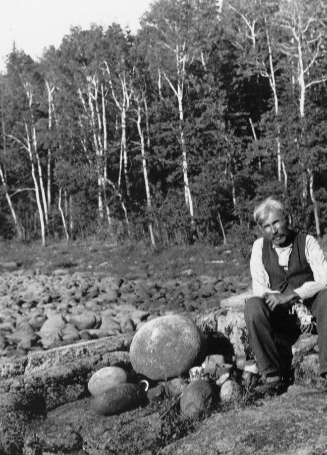 Il Capo William Berens seduto accanto alle pietre viventi dei suoi antenati; immagine scattata nel 1930 da Hallowell, tra Grand Rapids e Pikangikum, Ontario, Canada (American Philosophical Society)