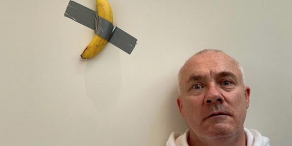 Damien Hirst con la replica della banana di Cattelan