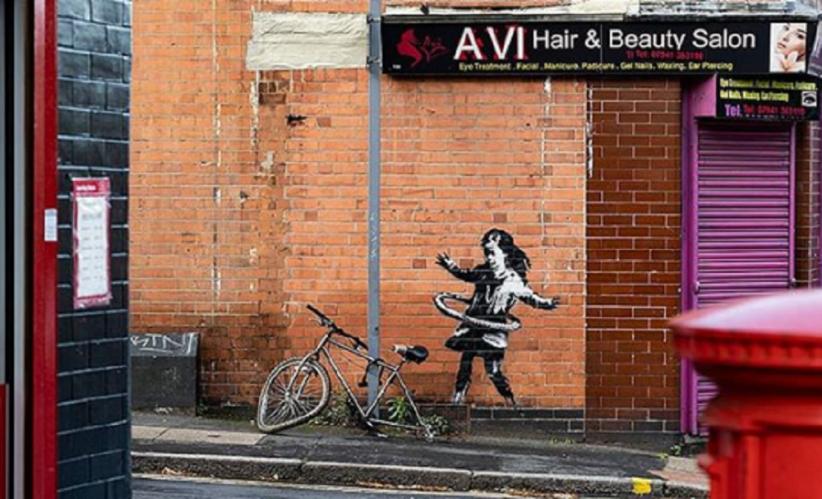 Murale di Banksy a Nottingham raffigurante una bambina che gioca con l'hula hoop con la ruota di una bicicletta