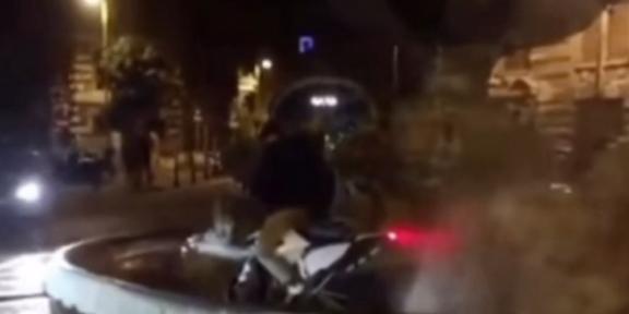 ragazzo con un motorino nella fontana delle rane del quartiere coppedè