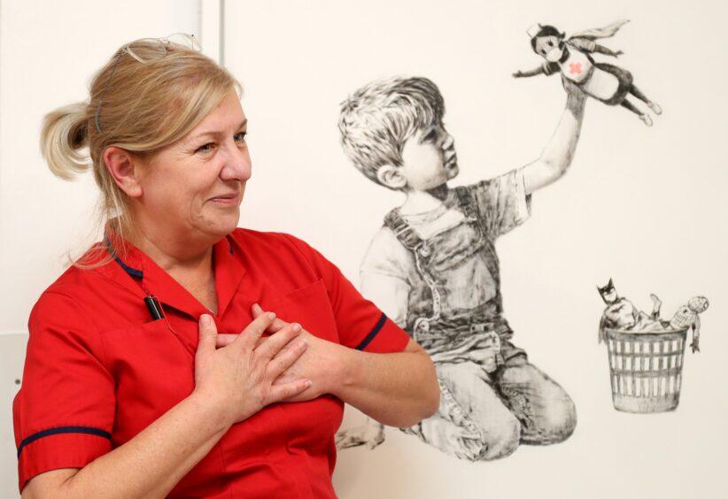"""infermiera posa davanti l'opera """"Game Charger"""" di Banksy"""