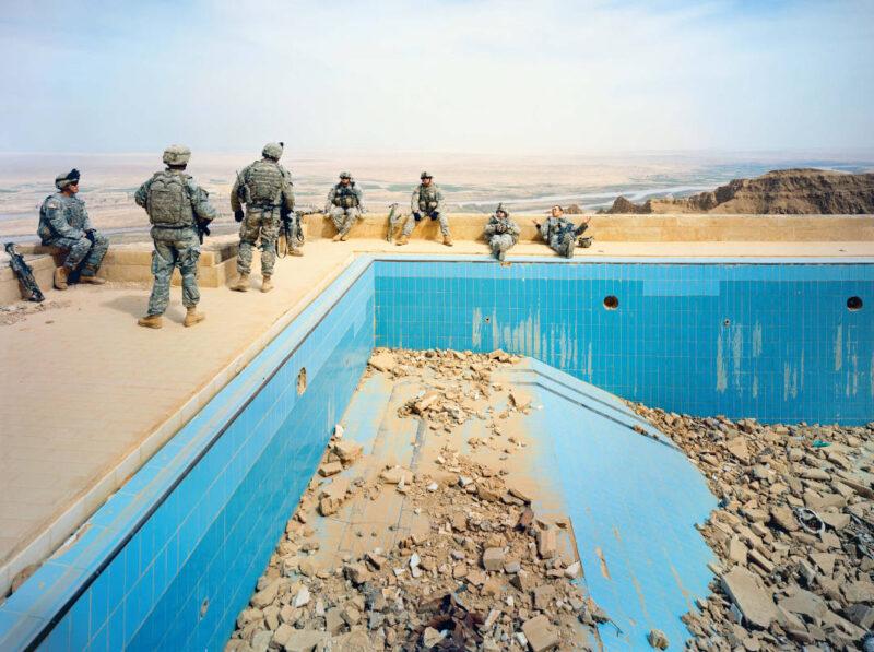 """Pool at Uday's Palace, Salah-a-Din Province, Iraq, 2009 Courtesy of the artist and Jack Shainman Gallery, New York Truppe della Compagnia Alfa, Secondo Battaglione, 27° Fanteria """"Wolfhounds"""" a riposo vicino alla piscina del palazzo di Uday Hussein, sulle montagne Jabal Makhoul, nella provincia di Salah-a-Din, Iraq centrale. Questa residenza estiva affacciata sulla valle del fiume Tigri è stata distrutta da bombe anti bunker JDAM americane all'inizio dell'invasione alleata dell'Iraq nel 2003, poiché si pensava che Saddam e il figlio potessero nascondersi in questa località remota. Noto per la sua crudeltà, Uday Hussein era il primogenito di Saddam."""