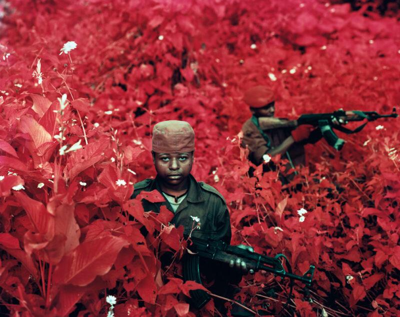 © Richard Mosse Vintage Violence, eastern Democratic Republic of Congo, 2011 * Courtesy of the artist and Jack Shainman Gallery, New York Giovani ribelli dell'Alleanza dei Patrioti per un Congo Libero e Sovrano (APCLS) in posa tra la vegetazione a Lukweti, territorio di Masisi, Kivu Nord. L'APCLS è un gruppo armato costituito da uomini della tribù Hunde che si sono ribellati a Joseph Kabila e al governo nazionale, ritenendolo vicino ai tutsi del Ruanda. Questa milizia è in guerra con l'esercito nazionale (FARDC) e la missione ONU in Congo (MONUSCO).