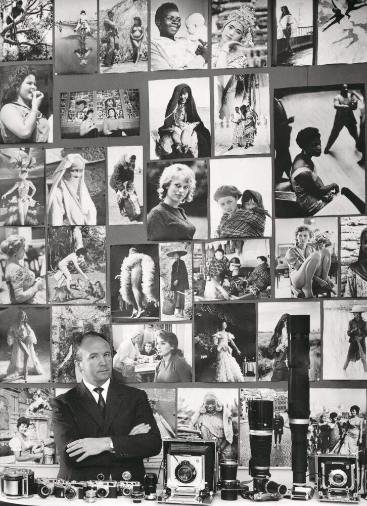 Mario De Biasi alla sua scrivania nella redazione di Epoca. In primo piano l'attrezzatura fotografica, alle spalle ritratti femminili raccolti nei cinque continenti, Milano, anni ' 60 © Archivio Mario De Biasi / courtesy Admira, Milano