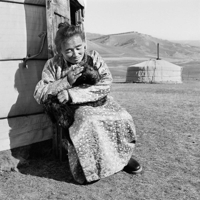 """Provincia del Hôvsgôl, Mongolia, 2017 """"I tempi stanno cambiando, non siamo più nomadi ma mi piace vivere qui, lontano dalla città, come ho vissuto per tutta la mia vita. Adoro stare fuori dalla mia iurta al tramonto; mi siedo qui insieme al mio gatto e alla mia capra e guardiamo il sole scendere."""" 150 x 150 cm ©Christian Tasso"""