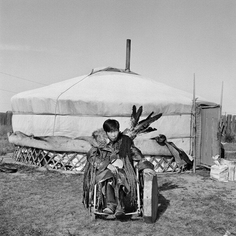 """Provincia del Dundgov', Mongolia, 2017 """"Sono diventato sciamano in giovane età. Non sapevo che lo sarei diventato, ma poi lo spirito mi ha scelto e mi sono ritrovato a scoprire nuovi aspetti sorprendenti e appassionanti di me, degli altri e della realtà che ci circonda. Mi piace il mio ruolo, sento di essere utile a molti e so di essere importante per la mia comunità."""" 150 x 150 cm ©Christian Tasso"""