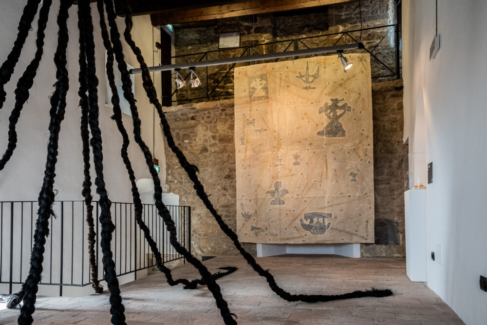 Binta Diaw, Uati's Wisdom (2020), Hair Extension, variable dimensions. Prima Torre-Torre Guaita, San Marin e Virginia Russolo, Mappa 7 (Map 7) (2021), 230 x 310 cm, Beeswax, wool wax, paper, pigments, spray paint on cotton
