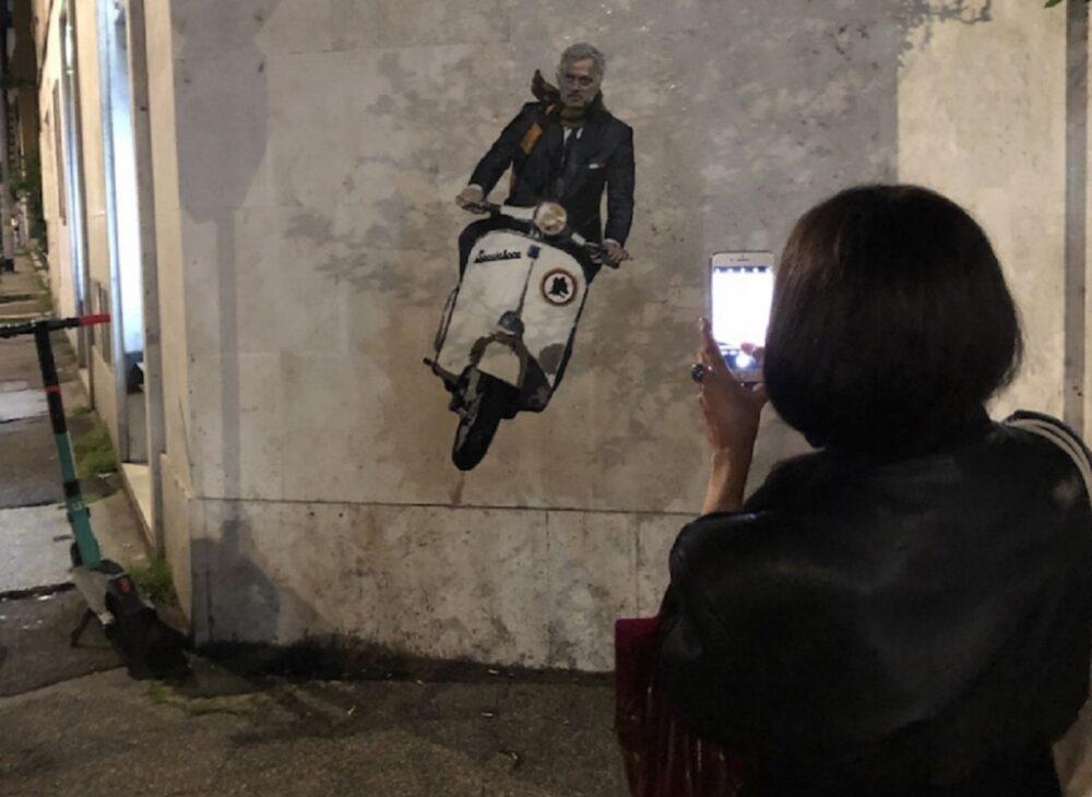Ragazza scatta una foto al murale dedicato a Mourinho nel rione Testaccio di Roma