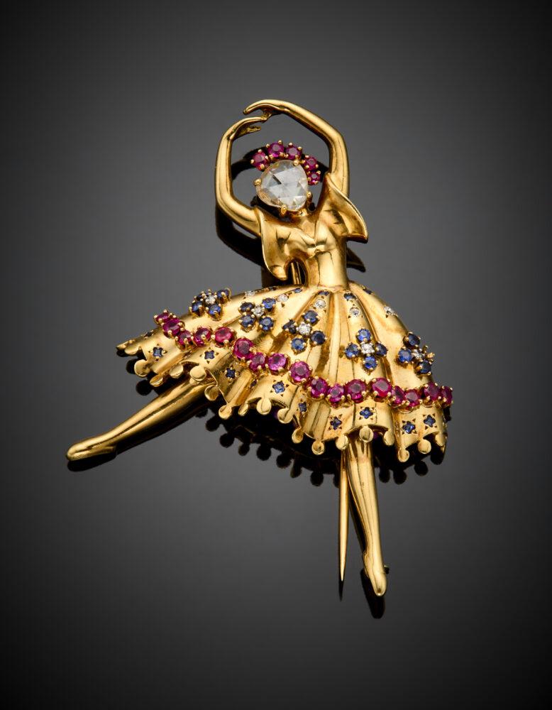 """Lotto 101 Van Cleef & Arpels Broche """"Ballerina"""" in oro giallo, il volto un diamante a mezza rosetta incorniciato da rubini, il tutù a frangia con diamanti, rubini e zaffiri, g 22,26 circa, lungh. cm 6,30 circa. Firmata e marcata Van Cleef & Arpels, n° 19119. Per confronto si veda: Alba Cappellieri 'Van Clle & Arpels. Il tempo, la Natura, l'amore' edizione Skira, pag. 162 e pag 165 Valutazione € 12.000 - 16.000"""